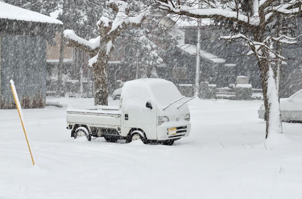 雪で真っ白な軽トラ